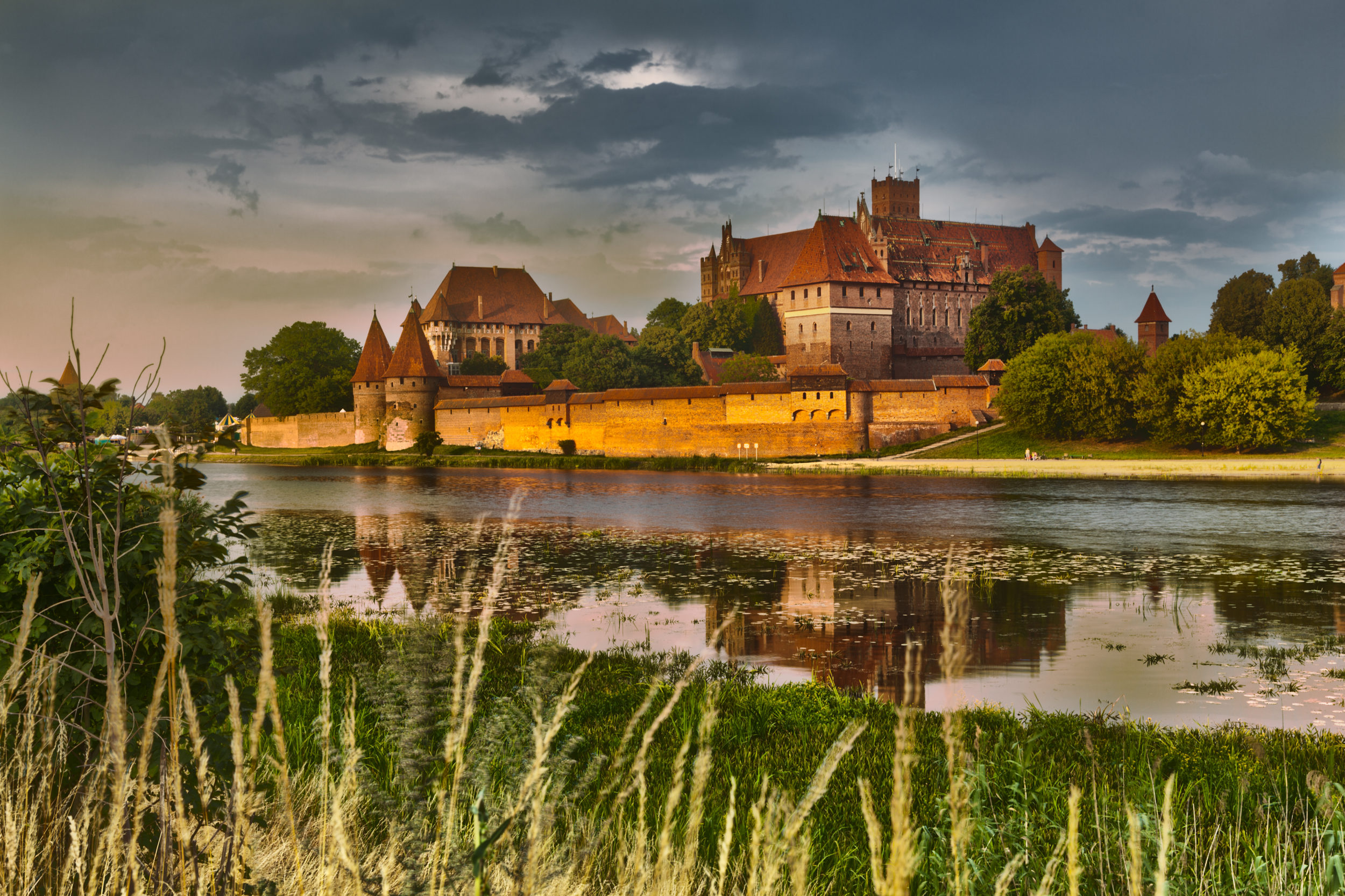 HDR image of medieval castle in Malbork at night with reflection in river